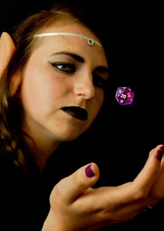 A young female dressed as an elf with a polyhedral twenty sided die often used in role playing games. Stock Photo