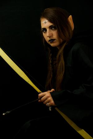 木の後ろに反らすの弓と矢とエルフとして服を着た若い女性