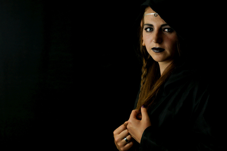 A young woman dressed as an elf with a black hooded robe and long hair with pointed elf ears Stock Photo