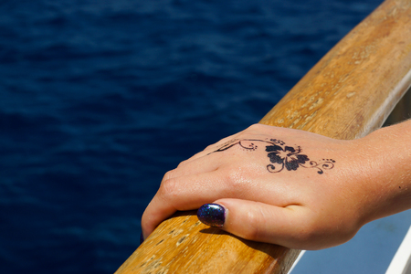 A photograph of a female hand holding onto the handrail of a boat in the Mediterranean sea, Malta. There is a floral design henna tattoo on the back of the hand.