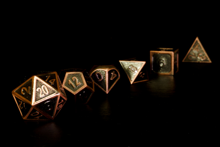 Een set polyedrale dobbelstenen op een leisteen oppervlak. Deze dobbelstenen worden gebruikt voor rollenspellen zoals Dungeons & Dragons. Stockfoto - 86044117
