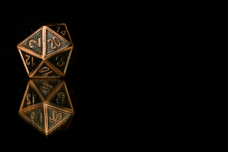 A twenty sided  polyhedral die on a mirrored surface. These type of dice are used for role playing games such as Dungeons & Dragons.