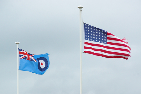 The flags representing the Royal Air Force and the United States Of America blow in the wind