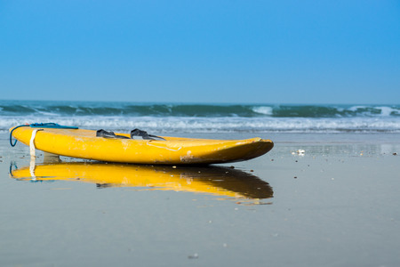 A yellow surfboard lays on Kotu Beach in The Gambia, West Africa Stock Photo