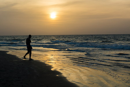 An african man is silhouetted as he walks along the shore of Kotu Beach in Gambia at sunset. Stock Photo
