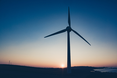 A turbine used to generate power is silhouetted by the sunset in Saltash, Cornwall Banco de Imagens