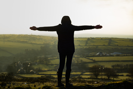 A young woman looks over the moors of Liskeard, Cornwall, UK with her arms outstretched Banco de Imagens