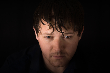 A young male looks at the camera with wet hair and water dripping in front of his face.