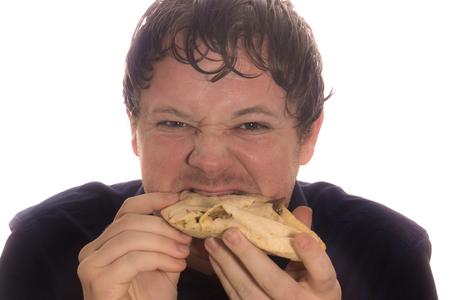 A young man eats a doner kebab