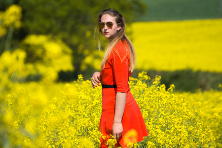 A young woman  wearing a red dress in the yellow fields of rapeseed.