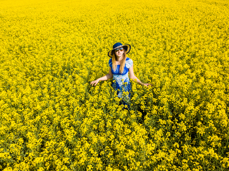 A young woman  wearing a blue dress in the yellow fields of rapeseed.