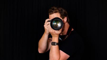 A professional photographer holds his camera close to his face. Banco de Imagens