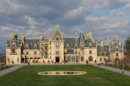 asheville: Biltmore House at the Biltmore Mansion in Asheville, North Carolina   Sun on the house and clouds in the sky