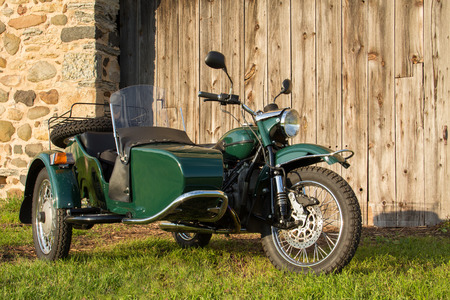 Sidecar motorcycle in front of fieldstone and weathered wood background