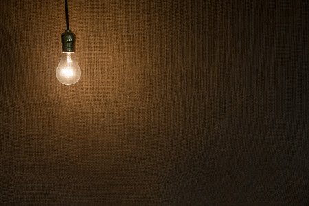 Hanging incandescent light bulb   Symbolic of ideas, creativity, and innovation   High texture background and a moody feel