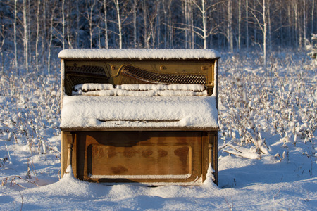 Upright piano that has been abandoned in a snowy winter field   meadow