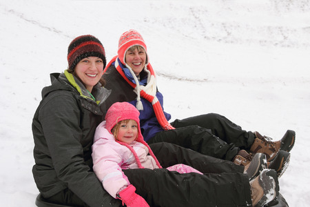 Mother, daughter, and granddaughter outdoors in the winter   Sledding, sitting, and smiling at camera  photo