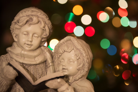 Statue of Christmas carolers   singers in front of Christmas tree with defocused lights  Stock Photo