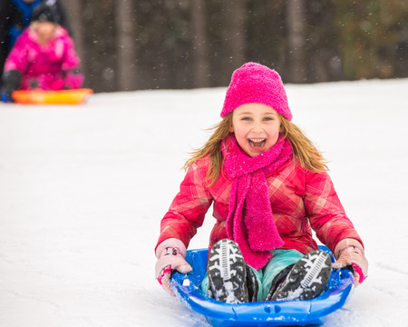 Happy girl expressing joy while sledding in the snow in winter  photo