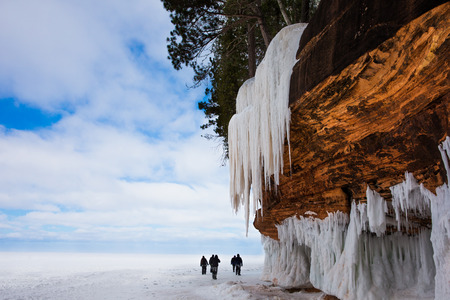 Frozen Lake Superior shoreline   Orange stone cliff, large icicles and people for scale   Copy space   Apostle Islands National Lakeshore on Lake Superior in Northern Wisconsin   Popular winter travel destination