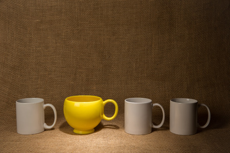 Coffee Mug Background   One unique yellow mug and three white ones in front of burlap with a spotlight on the yellow mug   Be unique