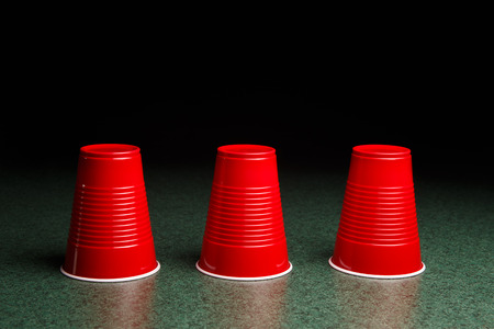 Shell Game - three red cups on a green table arranged like the shell game   Copy Space