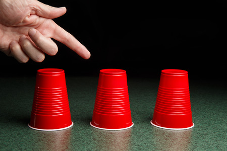 Shell Game - three red cups on a green table arranged like the shell game   Hand pointing to the center cup   Copy Space