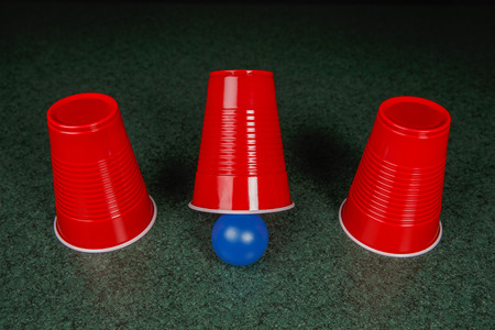 Shell Game - three red cups and a blue ball on a green table arranged like the shell game.  Gambling.  Copy Space. Stock Photo