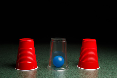 Life is easy when you know the answers.  Location of blue ball is revealed by clear cup.  Copy space. Stock fotó