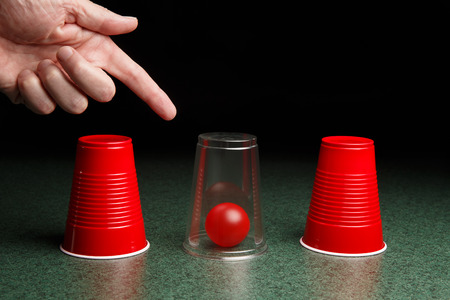 seeking an answer: Life is easy when you know the answers.  Location of red ball is revealed by clear cup and pointing hand.  Copy space.