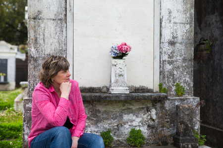Woman in historic New Orleans cemetery   Copy space on crypt if needed  photo