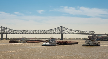 Commercial shipping on Mississippi River at New Orleans.  Barge and tug traffic beneath bridge.  Copy space at top.