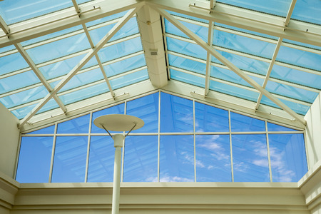 Blue sky viewed through glass ceiling and wall of a modern building.