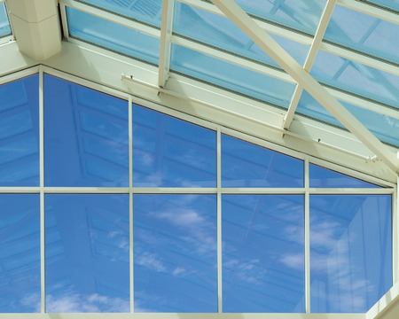 Blue sky viewed through glass wall and ceiling of a modern building.