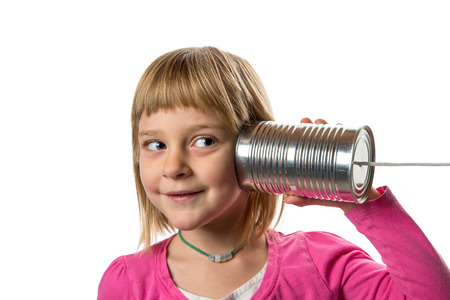 Young girl listening to tin can  string phone.  Isolated against white background.  Copy space to left.