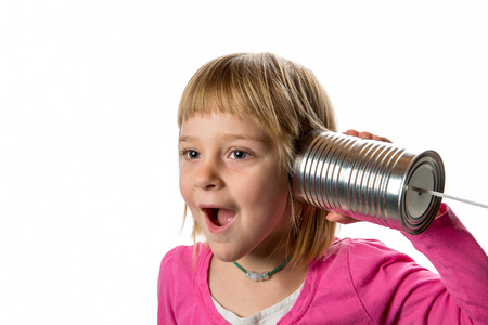 Young girl listening to tin can  string phone.  Expressing surprise.  Isolated against a white background.  Copy space to left.