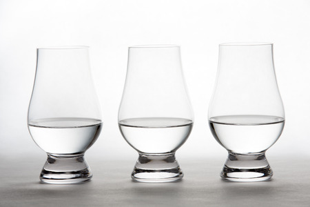 crystal background: Three backlit crystal glasses containing vodka, gin, or tequila. Stock Photo