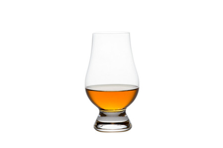 Crystal glass containing whiskey, bourbon, or other amber liquor.  Isolated on white.