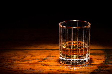 Liquor in a straight-cut tumbler on a textured wooden table.  Spot light focused on the glass.  Copy space on left.  Upper frame fades to black.