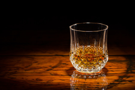 Liquor in a diamond-cut tumbler on a textured wooden table.  Spot light focused on the glass.  Copy space on left.  Upper frame fades to black.