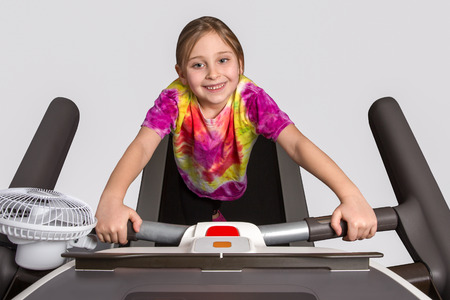 cardiovascular exercising: Young girl in tie dyed shirt exercising on a treadmill.  Isolated studio shot. Stock Photo