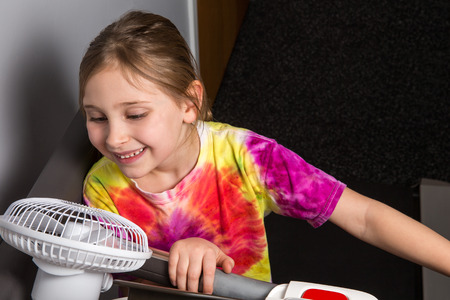 cardiovascular exercising: Young girl exercising on treadmill cooling off with fan.  Colorful shirt.  Copy space in upper right.