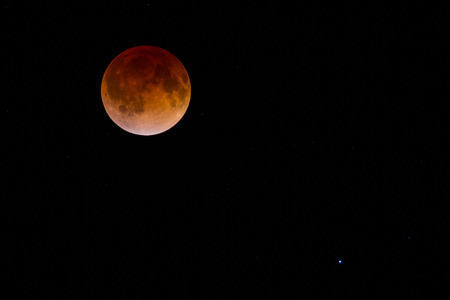 Red Blood Moon caused by total lunar eclipse.  Many visible faint stars.  The bright star in the lower right is Spica, the brightest star in the constellation Virgo.