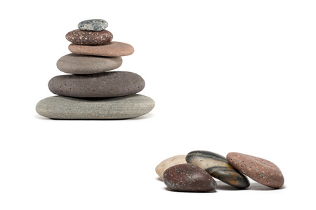 zen stones: Stone cairn made from a variety of colorful Lake Superior rocks.  Four extra stones in foreground. Studio shot.  Isolated on white.