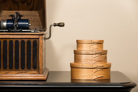 antique phonograph: Vintage hand-crafted shaker boxes next to antique cylindrical phonograph.  Copy space in upper right.