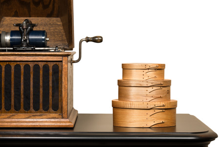 Vintage hand-crafted shaker boxes next to antique cylindrical phonograph.  Retro craftsmanship.  Isolated on white.