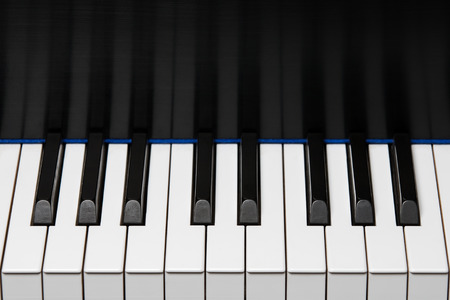 upper half: Section of piano keyboard showing one octave plus two extra keys on each end.  Key reflection in backboard.  Copy space in upper half of frame.