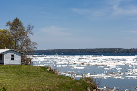 breaking up: Ice breaking up on a bay in the Spring.   Small house overlooking the scene.  Copy space in upper part of frame.