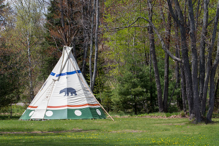 Indian tepee in upper Midwest USA State Park.  Bear clan symbol on tent.