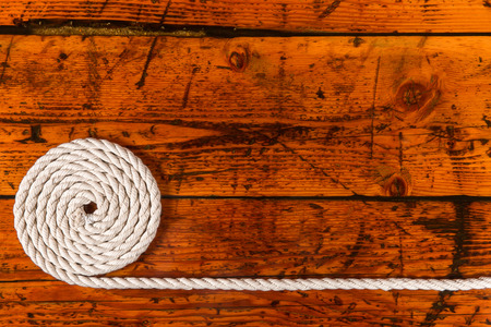 coiled rope: Coiled, white rope on a highly textured wooden background.  Copy space on right.  Nautical theme.